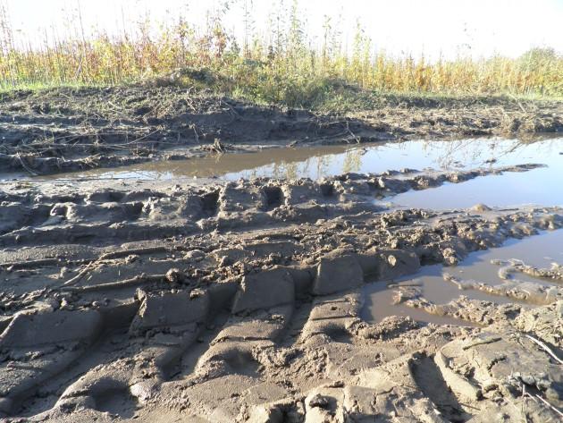 Trekkersporen met plassen in het land