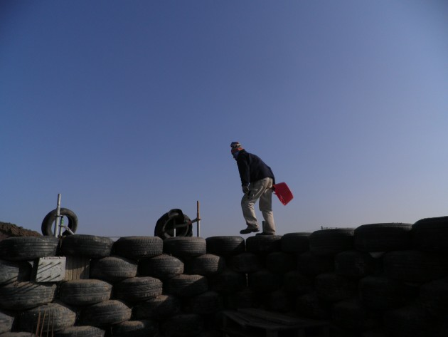 Een werker op weg over bandenwand in aanleg